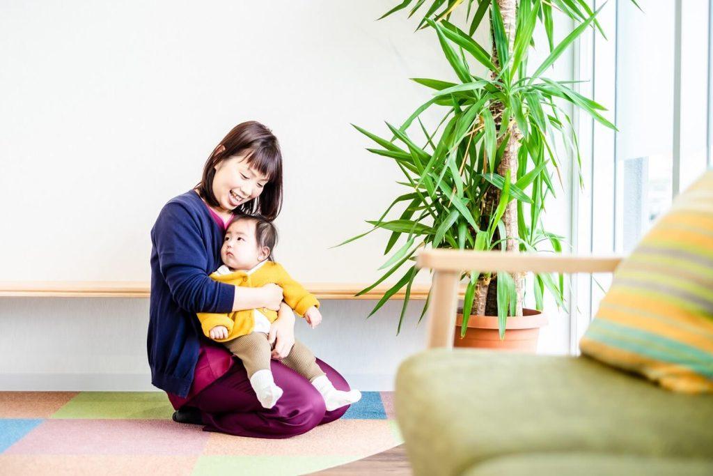 キッズスペースで赤ちゃんを抱っこする羽場さん