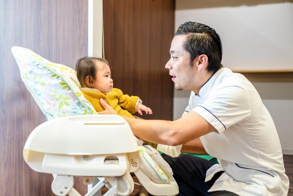 座ってハイローチェアに座っている赤ちゃんをあやすみやもと鍼灸整骨院院長