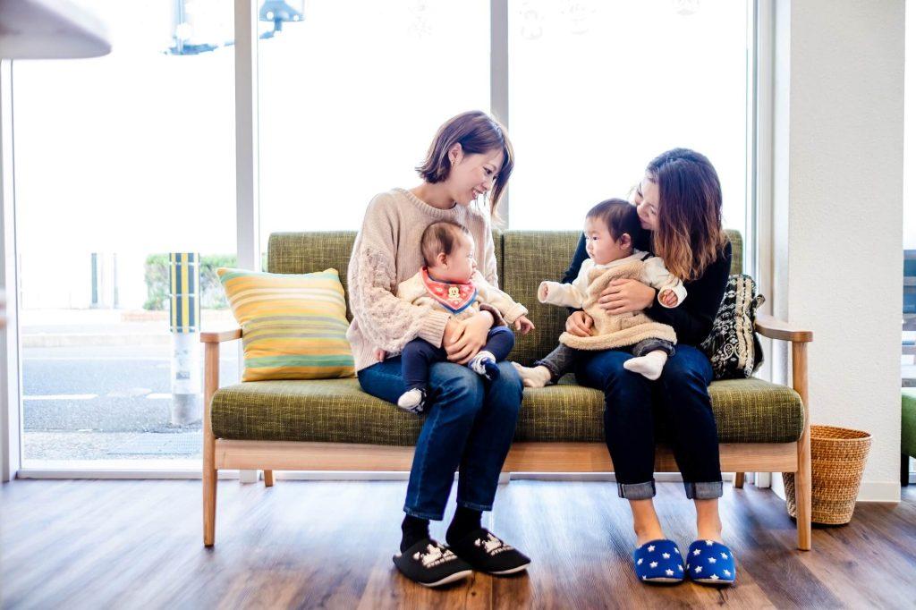 待合室のソファに座って、それぞれ赤ちゃんを抱っこしながら談笑する2人のママさん