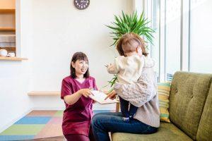 待合の産後骨盤矯正のママさんに問診表を渡す受付の羽場さん