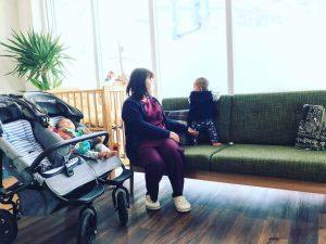 待合室のソファで双子の赤ちゃんを見る受付の羽場さん
