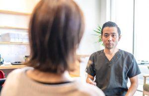 産後骨盤矯正のママさんの問診をする院長