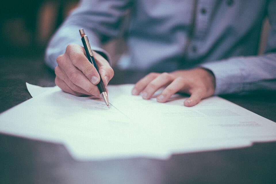 腰痛にコルセットが効果的な理由をペンを片手にまとめている写真