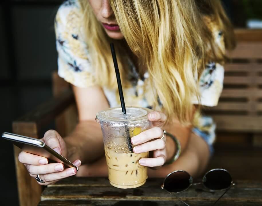 左手でコーヒーボトルを持ちながら、右手でスマホを操作する女性