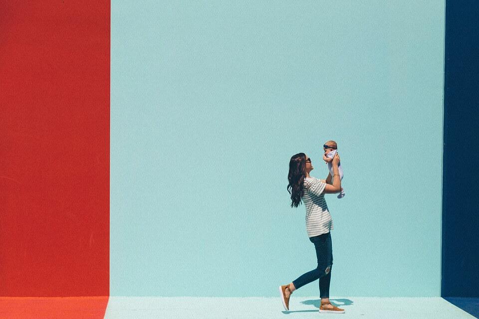 赤ちゃんを抱っこしながら歩く女性