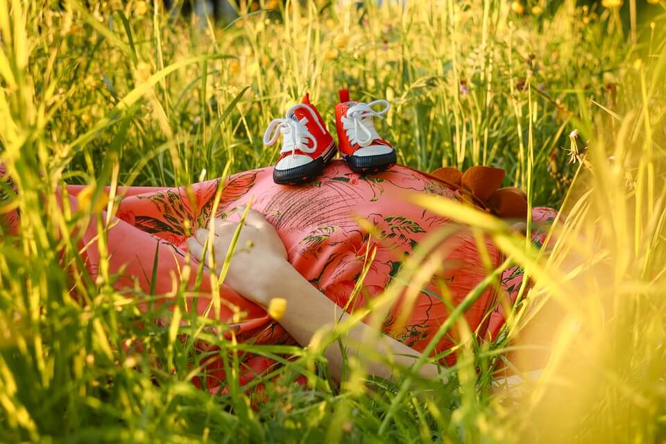 子ども靴をお腹の上に乗せながら寝ている妊婦さん