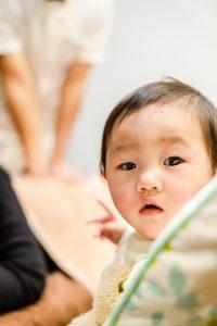 赤ちゃん越しに見える産後骨盤矯正を受けているママさん