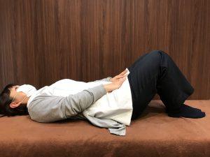 膝を曲げて仰向けに寝て、両太ももの前面に両手を置いている受付の羽場さん