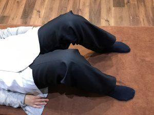 足幅を少し広げて膝を曲げて仰向けに寝る受付さん