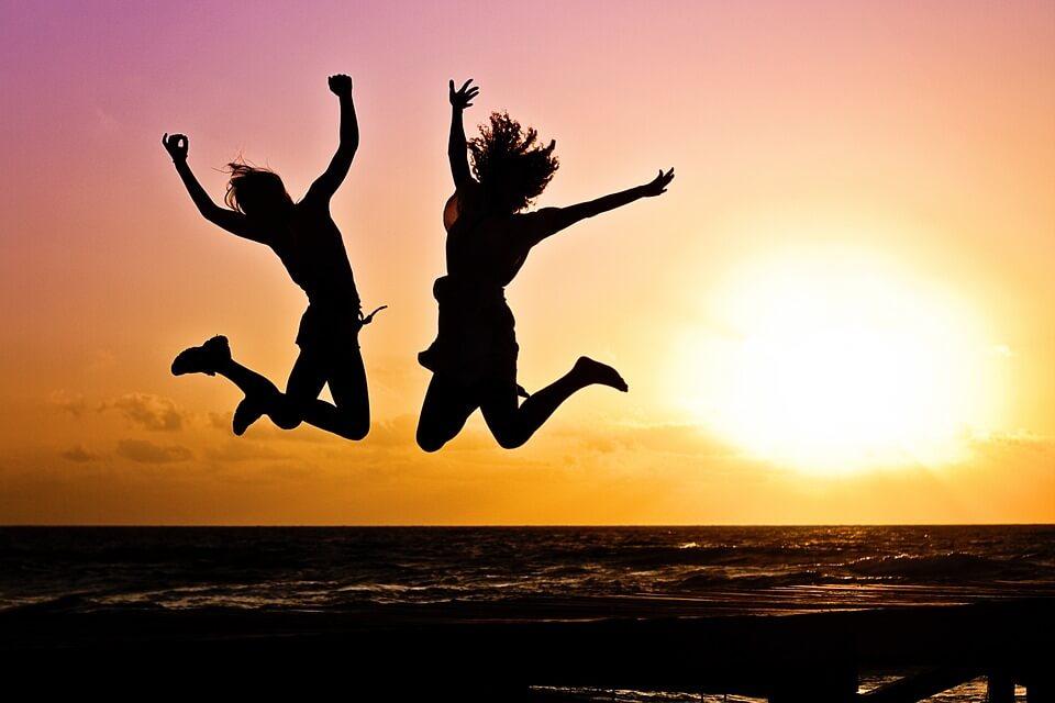 夕方の海でジャンプする2人の女性