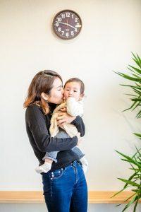 産後骨盤矯正前にははけなかったデニムをはいて抱っこする赤ちゃんにキスをするママさん