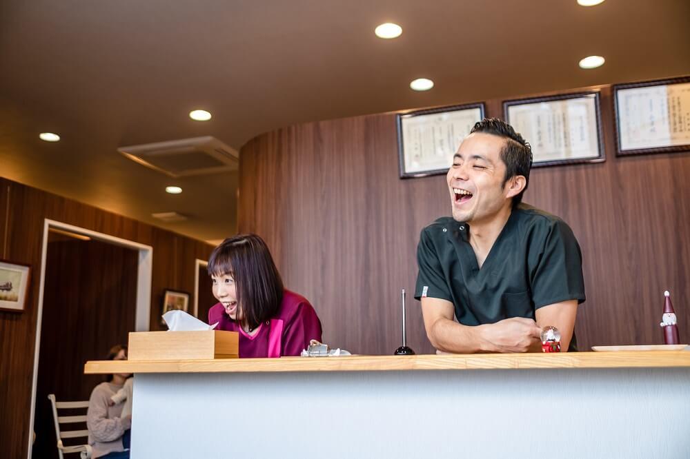 受付台で笑う京都長岡京市にあるみやもと鍼灸整骨院院長と受付さん