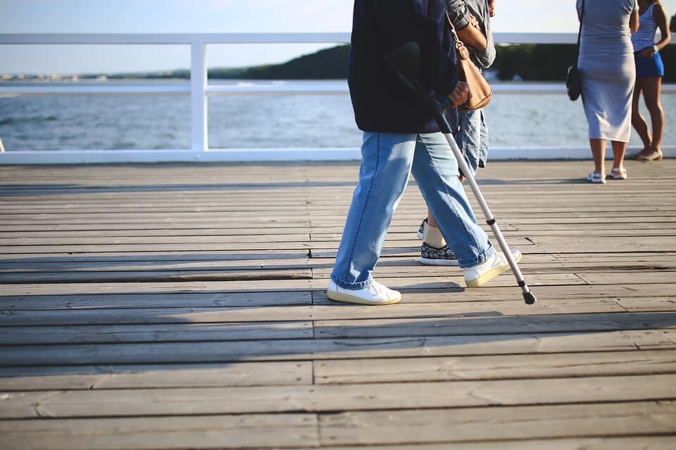 海辺の桟橋を松葉杖で散歩する女性