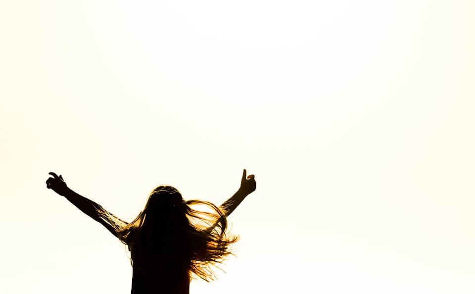 両手を挙げて喜ぶ女性の後ろ姿