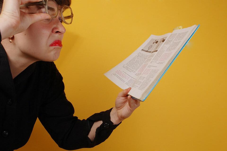 左手に持ったパンフレットを読みにくそうにする女性