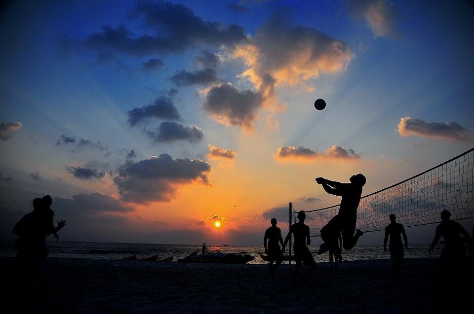 夕方ビーチでバレーボールをする男性たち