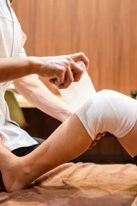 スポーツ障害の患者様の膝へ包帯をする院長の右手